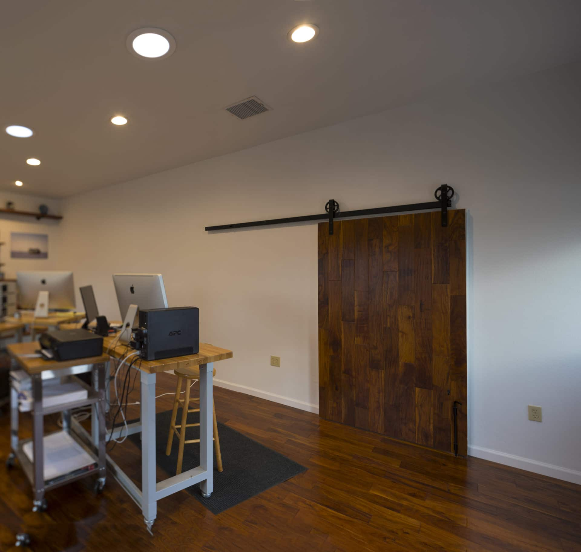 remodeled office space with attractive pipe shelving and rustic barn door